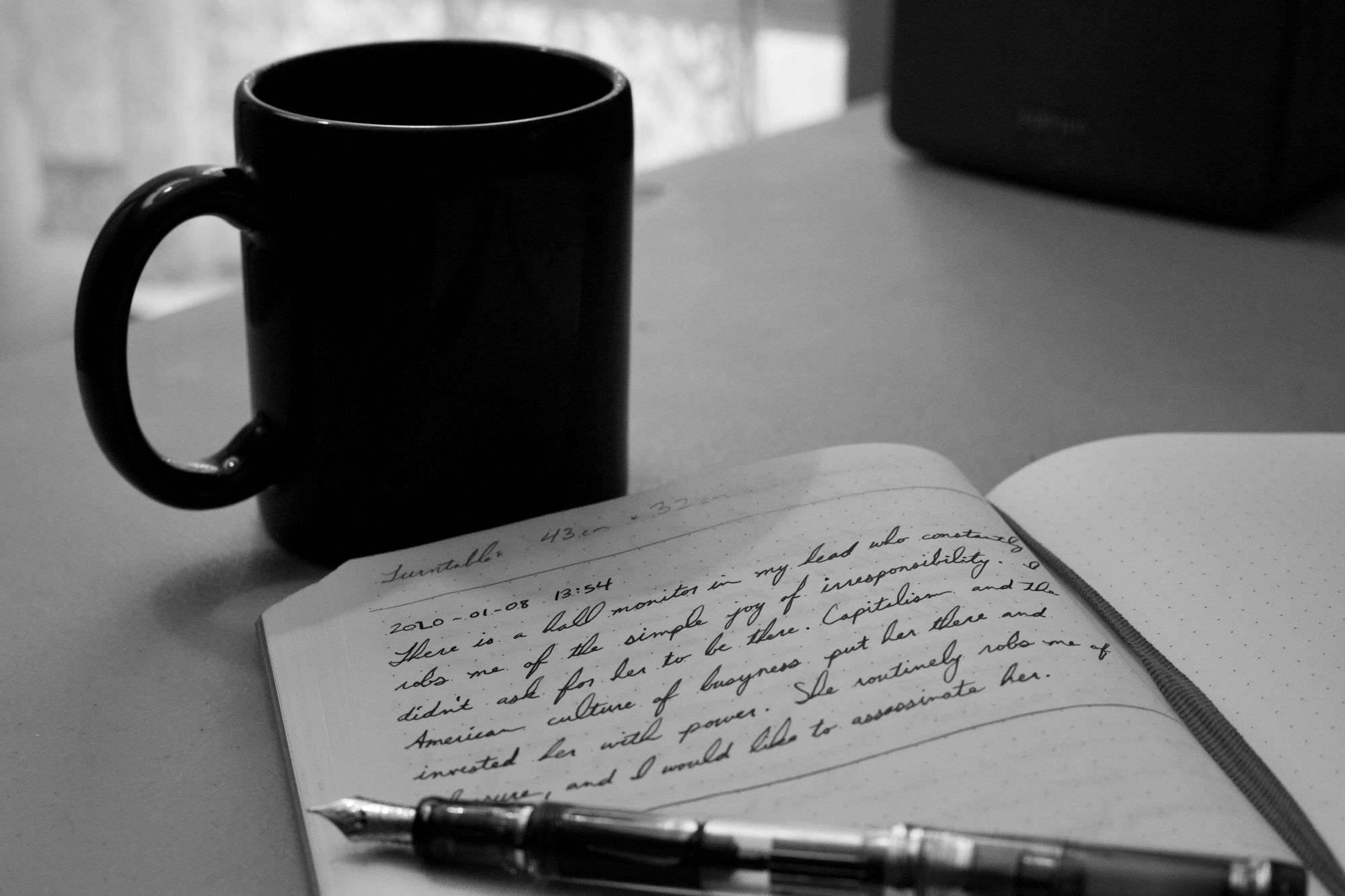 Notebook with cursive handwriting, a fountain pen, and a coffee mug
